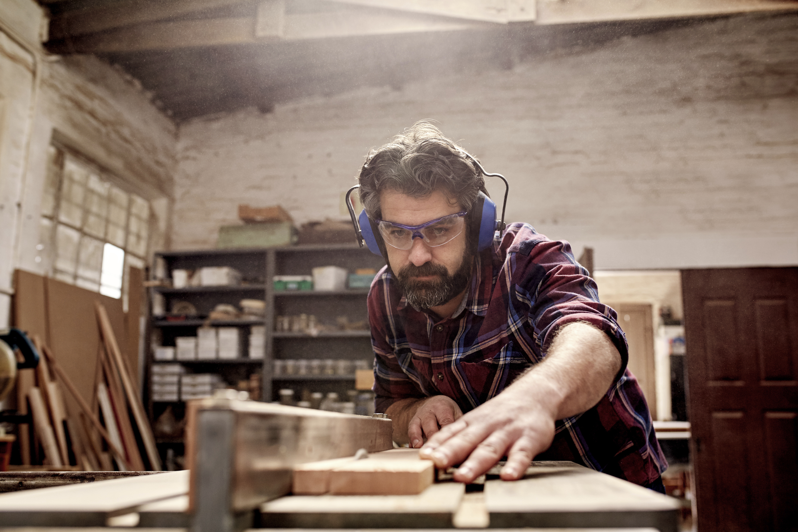 Carpentry business owner cutting a plank of wood in workshop